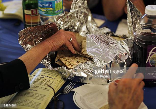People take part in eating matzo during a community Passover Seder at Beth Israel synagogue on March 25 2013 in Miami Beach Florida The community...
