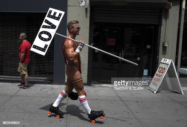 People take part in the annual 2018 New York City Pride Parade on June 24 2018 as they make their way down 7th Avenue in New York