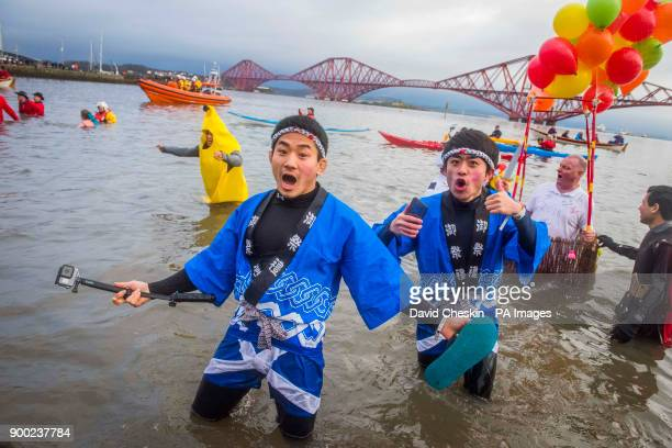 People take part in the annual Loony Dook swim in Firth of Forth Scotland
