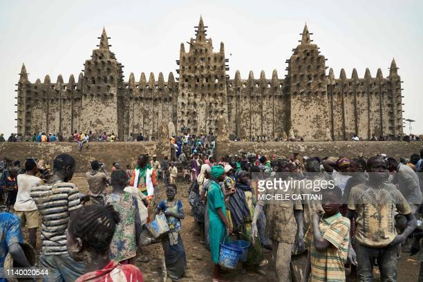 People take part in the annual rendering of the Great Mosque of Djenne in central Mali on April 28 2019 Several thousand residents of the historic...