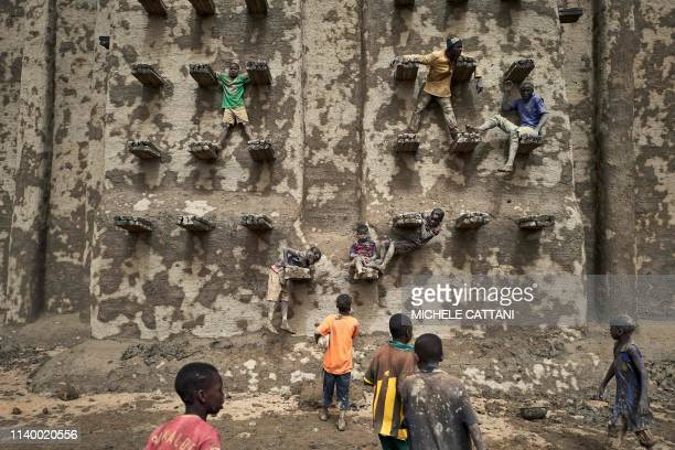 TOPSHOT People take part in the annual rendering of the Great Mosque of Djenne in central Mali on April 28 2019 Several thousand residents of the...