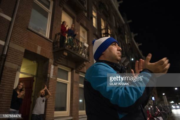 People take part in the #applausvoordezorg campaign and applaud healthcare employees during the COVID19 coronavirus outbreak in Amsterdam on March 17...