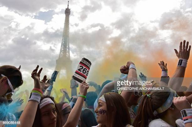 People take part in the Color Run 2017 's edition in front of the Eiffel Tower in Paris on April 16 2017 The Color Run is a five kilometres paint...