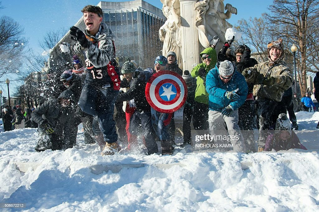 TOPSHOT - People take part in the DC Snowball Fight on Dupont Circle in Washington on January 24, 2016. Snowball fights have become a tradition after every major snow storm in the Nation's Capital. A massive blizzard that claimed at least 16 lives in the eastern United States finally appeared to be winding down Sunday, giving snowbound residents the chance to begin digging out. / AFP / Nicholas Kamm