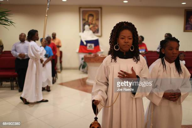 People take part in the entrance procession during a service at the Notre Dame D'Haiti Catholic Church as they celebrate Haitian Flag day in the...