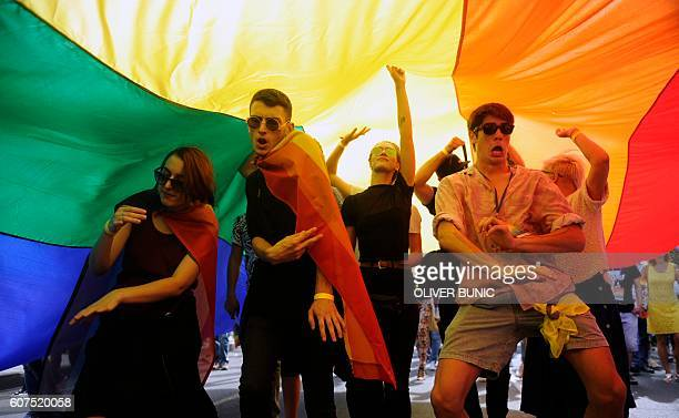 People take part in the Gay Pride parade under a huge rainbow flag in Belgrade on September 18 2016 The Belgrade Gay Pride parade the third in a row...