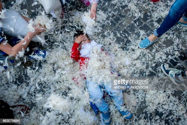 People take part in the International Pillow Fight event on April 1 in Bucharest Romania / AFP PHOTO / ANDREI PUNGOVSCHI