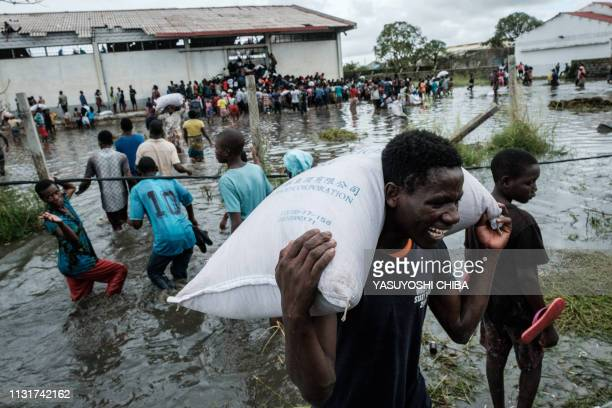 People take part in the looting sacks of Chinese rice printed China Aid from a warehouse which is surrounded by water after cyclone hit in Beira...