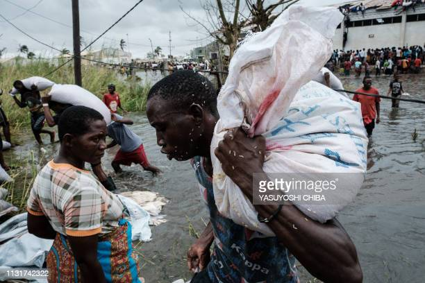 TOPSHOT People take part in the looting sacks of Chinese rice printed China Aid from a warehouse which is surrounded by water after cyclone hit in...