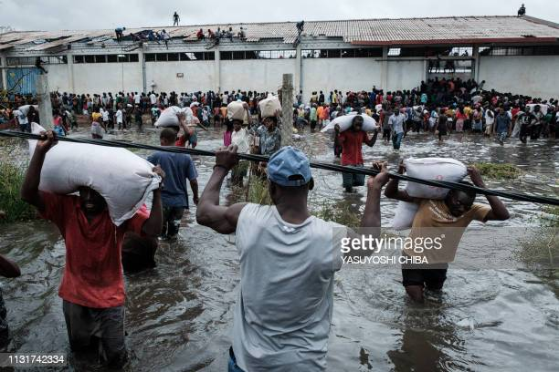 "People take part in the looting sacks of Chinese rice printed ""China Aid"" from a warehouse which is surrounded by water after cyclone hit in Beira,..."