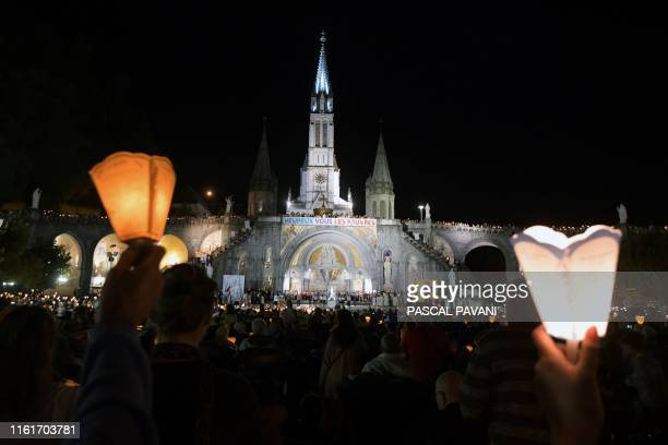 TOPSHOT People take part in the Marian procession in the shrine of Our Lady of Lourdes during the annual Catholic pilgrimage of Lourdes on August 14...