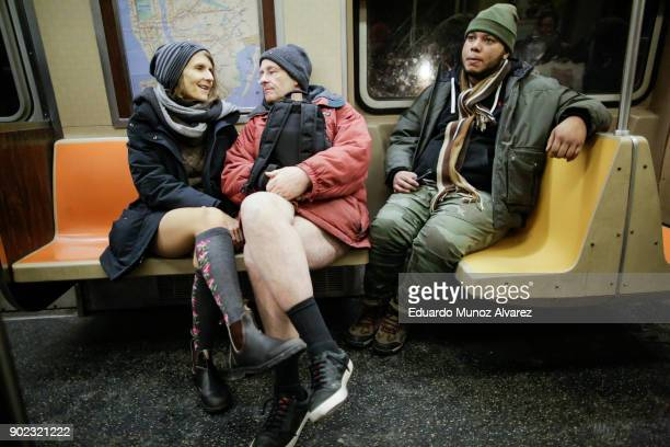 People take part in the No Pants Subway Ride braving freezing temperatures as others are seen covered for cold weather on January 7, 2018 in New York...