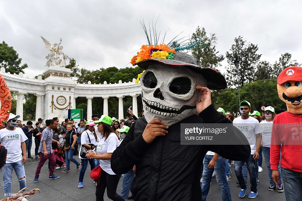 People take part in the tenth Monumental 'Alebrijes' Parade and contest organized by the Folk Art Museum, on October 22, 2016 in Mexico City. More than two hundreds 'Alebrijes' -Mexican folk art traditional sculptures representing fantastical creatures - take part in the event. / AFP / YURI
