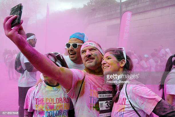 People take part in the third edition of the Paris Colour Run along the waterfront between City Hall and the Eiffel Tower on April 17 2016 in Paris...
