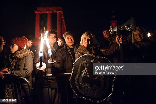 People take part in the torchlight procession as it makes its way through Edinburgh for the start of the Hogmanay celebrations on December 30 2014 in...