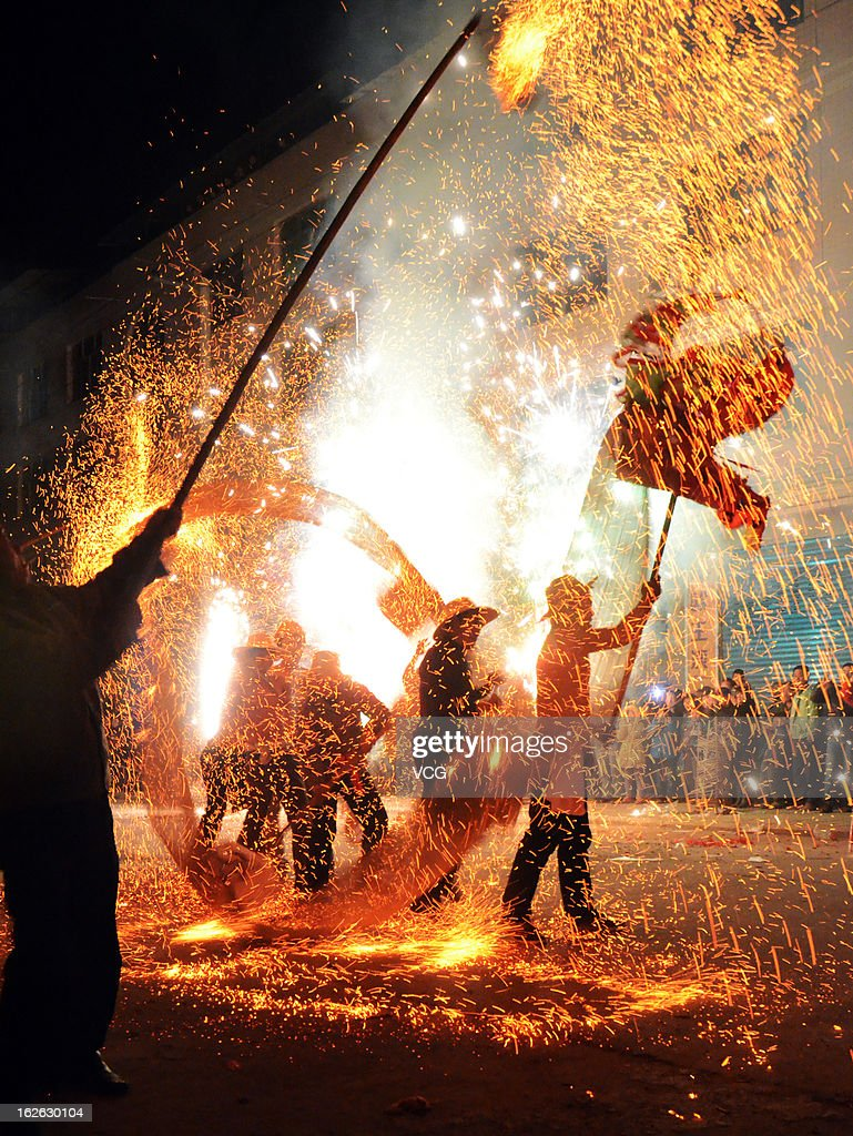 People take part in the traditional dragon dance in the molten iron on February 24, 2013 in Dazhou, Sichuan Province of China. The dragon dance in the molten iron, 'Wu Huo Long' in Chinese, is a traditional custom to celebrate the Lantern Festival. The Chinese Lunar New Year also known as the Spring Festival, which is based on the Lunisolar Chinese calendar, is celebrated from the first day of the first month of the lunar year and ends with Lantern Festival on the Fifteenth day. 2013 is the Year of the Snake according the 12-year cycle of animals which appear in the Chinese Zodiac.