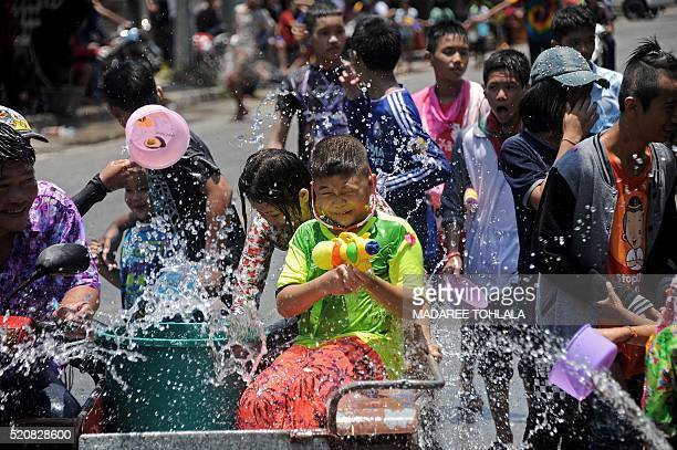 People take part in water battles as they celebrate Songkran the Thai new year in Narathiwat southern Thailand on April 13 2016 Thais and tourists...