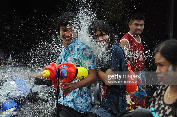 People take part in water battles as they celebrate the Songkran festival in Narathiwat southern Thailand on April 13 2013 Songkran the Thai new year...