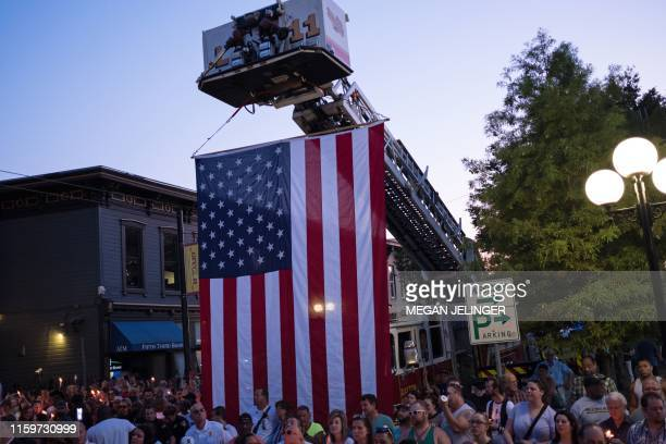 People take part of a candle lit vigil in honor of those who lost their lives or were wounded in a shooting in Dayton Ohio on August 4 2019 The...