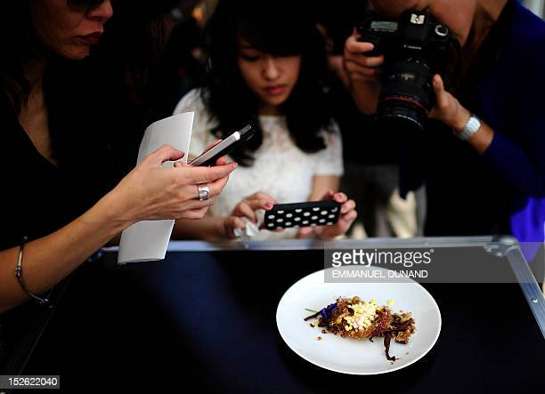 People take photo of a dish created by French chef Dominique Crenn from Atelier Crenn in San Fransisco during a cooking demonstration as part of the...