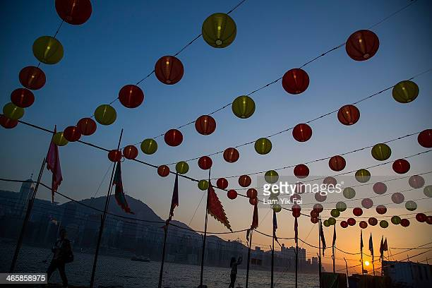 People take photograph under the lanterns displayed for the Lunar New Year as China prepares for the Year of the Horse at Wet Kowloon waterfront...