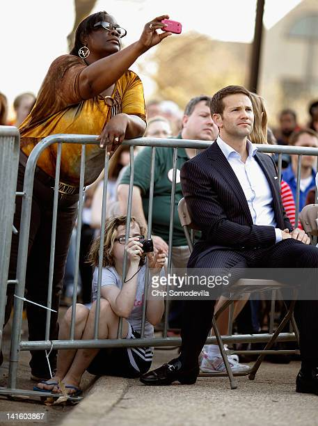 People take photographs as Rep Aaron Schock listens to Republican presidential candidate former Massachusetts Gov Mitt Romney during a townhall...