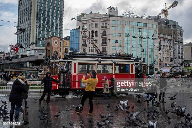 People take photographs as the famous Istiklal street tram passes by on December 17 2015 in Istanbul Turkey With the economy expected to grow Turkey...