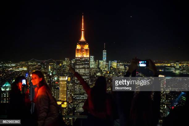People take photographs as the spires of the Empire State Building center left and One World Trade Center center right stand lit in orange to support...