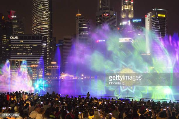 People take photographs as they watch the Spectra light and water show at the Marina Bay waterfront at night in Singapore on Friday Feb 16 2018...