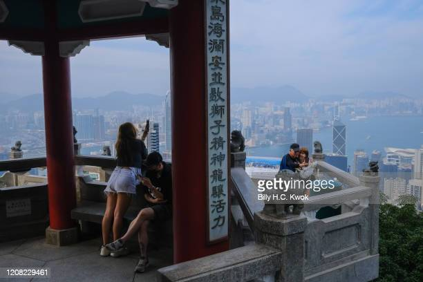 People take photographs as Victoria harbour is seen at the background during a coronavirus outbreak on March 26 2020 in Hong Kong China Latest...