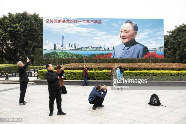 People take photographs in front of a billboard featuring an image of China's former leader Deng Xiaoping in Shenzhen, China, on Friday, Dec. 14,...