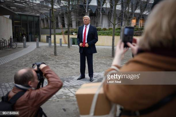 People take photographs of a model of US President Donald Trump from the Madame Tussaud's waxwork attraction as it stands outside the new US embassy...