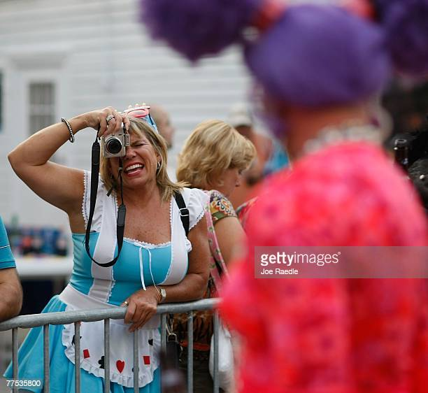 People take photographs of a person dressed in a costume as they participate in the Fantasy Fest Masquerade March in Key West Florida October 27 2007...