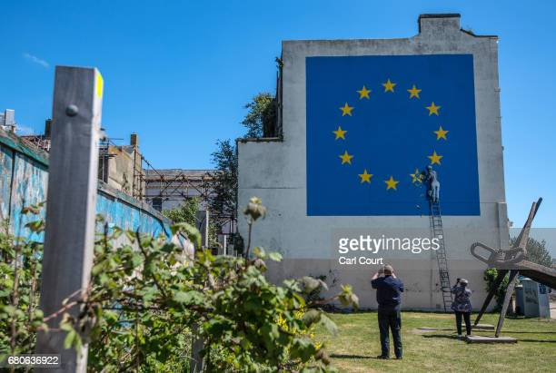People take photographs of a recently painted mural by British graffiti artist Banksy depicting a workman chipping away at one of the stars on a...