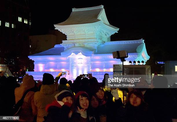 People take photographs of a snow statue of illuminated Kasuga Taisha at Odori Park ahead of the 66th Sapporo Snow Festival on February 4 2015 in...