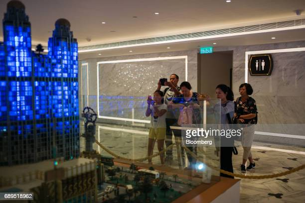 People take photographs of an illuminated Lego model of Studio City casino resort developed by Melco Crown Entertainment Ltd at the resort in Macau...