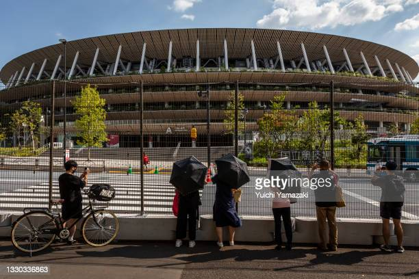 People take photographs of Olympics Stadium through a security fence on July 24, 2021 in Tokyo, Japan. As the postponed Tokyo Olympics get underway...