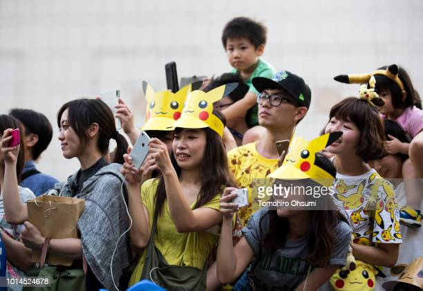 People take photographs of performers dressed as Pikachu a character from Pokemon series game titles marching during the Pikachu Outbreak event...