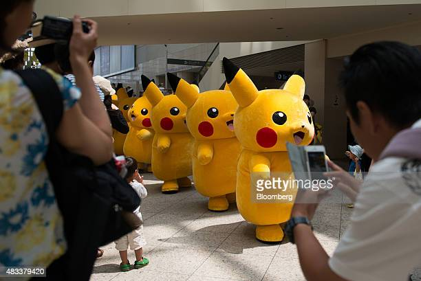 People take photographs of performers dressed as Pikachu a character from Nintendo Co's Pokemon game title marching through a shopping mall during...