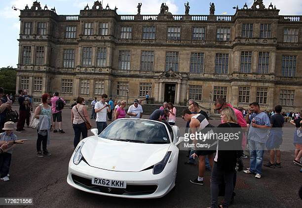 People take photographs of the car driven by BBC Radio Two DJ Chris Evans in front of Longleat House at Longleat Safari Park that are being driven...