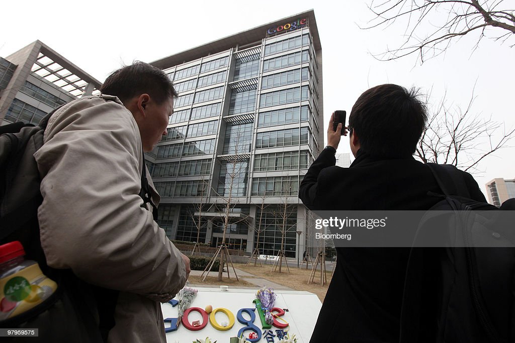 People take photographs of the Google Inc. sign outside the company's offices in Beijing, China, on Tuesday, March 23, 2010. Google Inc., following through on a pledge to stop censoring search results in China, began serving mainland Chinese users via its unfiltered Hong Kong site, a move that could prompt the government to block the service. Photographer: Doug Kanter/Bloomberg via Getty Images