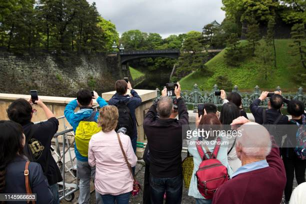 People take photographs of the Imperial Palace on April 30 2019 in Tokyo Japan Japan's 85yearold Emperor Akihito became the first Japanese emperor to...