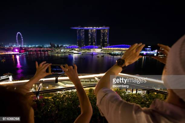People take photographs of the Marina Bay Sands hotel and casino center and Singapore flyer illuminated at night in Singapore on Wednesday June 13...
