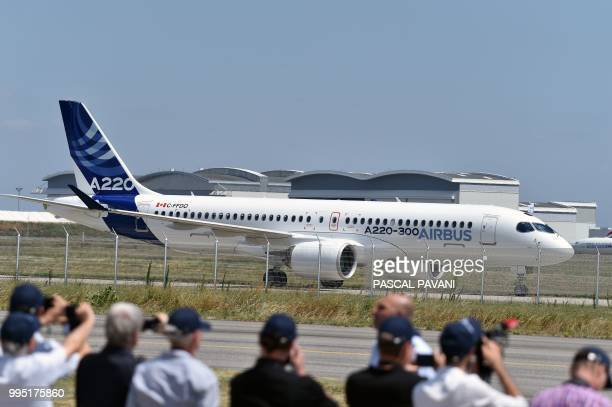People take photographs of the new Airbus A220300 on the tarmac during its presentation on July 10 2018 at the Airbus delivery centre in Colomiers...