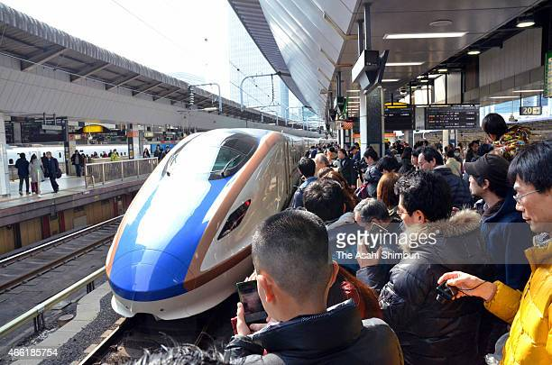People take photographs of the new Hokuriku Shinkansen bullet train approaching to a platform at Tokyo Station on March 14 2015 in Tokyo Japan A...