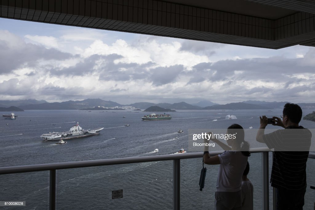 People take photographs of the People's Liberation Army (PLA) Liaoning aircraft carrier, left, as it sails into Hong Kong, China, on Friday, July 7, 2017. The carrier will visit Hong Kong between July 7 and 11. Photographer: Justin Chin/Bloomberg via Getty Images