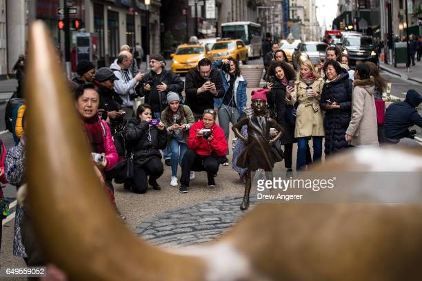 People take photographs of the 'The Fearless Girl' statue as it stands across from the iconic Wall Street charging bull statue March 8 2017 in New...