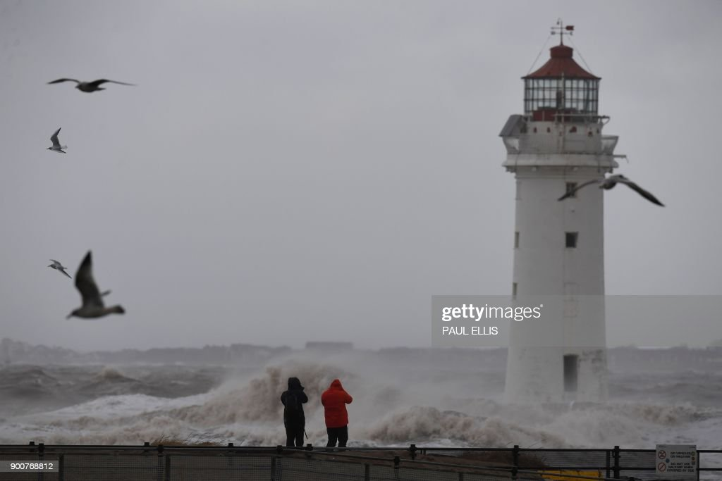 People take photographs of the waves in a stormy sea alongside the lighthouse in New Brighton, north west England, on January 3, 2018, as Storm Eleanor swept over the country. Storm Eleanor swept across the country overnight, bringing winds of up to 100 mph in places and carrying rain, hail and thunder and lightning. / AFP PHOTO / Paul ELLIS