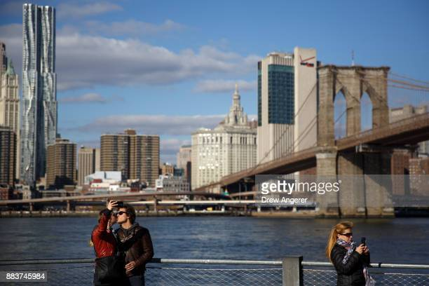 People take photographs on their smartphones along the East River near the Brooklyn Bridge December 1 2017 in the Brooklyn borough of New York City...