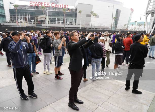 people take photos a screen as Former NBA player Kobe Bryant is remembered outside the 62nd Annual GRAMMY Awards at STAPLES Center on January 26 2020...
